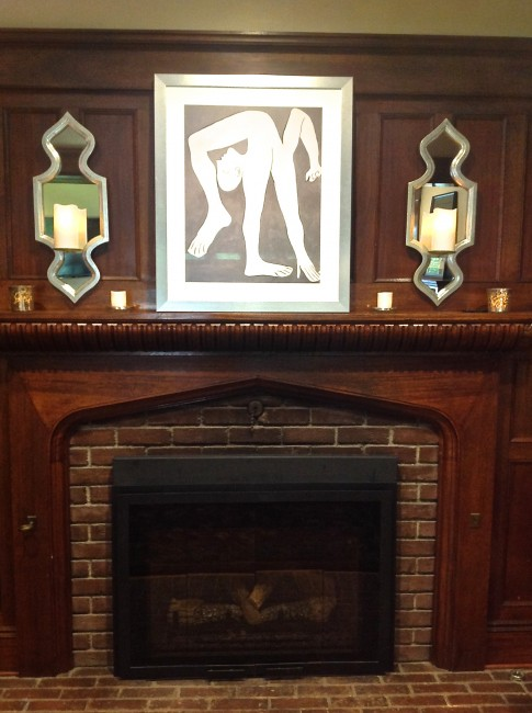 Inglenook detail:  The art print and candle sconces pop against the dark wood.